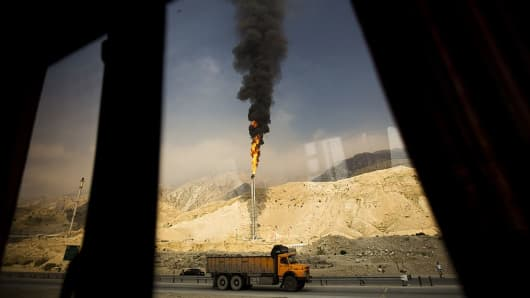 A gas flame is seen through a bus window in the South Pars gas field facilities in the southern Iranian port of Assaluyeh on the shore of the Gulf on January 22, 2014.
